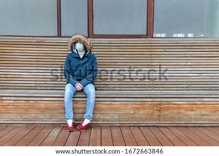 Sick man with hood sitting alone on bench, wearing facial mask against transmissible infectious diseases, covid-19. Empty city from people due to coronavirus pandemic. Life in isolation and quarantine #1672663846