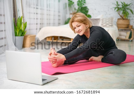 Fitness training online, senior woman at home with laptop. #1672681894