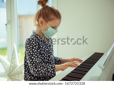 Little cute child girl playing piano with maskat quarantine because of coronavirus #1672725328