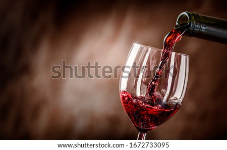 Pouring red wine into the glass against rustic background.  Pour alcohol, winery concept. #1672733095