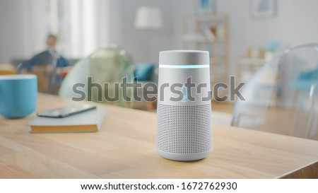 Shot of a Smart Speaker with Artificial Intelligence Assistant Standing on the Table in Bright Cozy Living Room. #1672762930