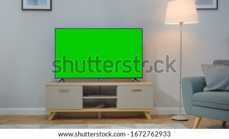Shot of a TV with Horizontal Green Screen Mock Up. Cozy Living Room at Day Time with a Chair and Lamps Turned On at Home.