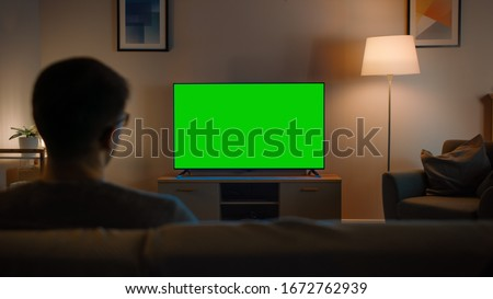 Young Man in Glasses is Sitting on a Sofa and Watching TV with Horizontal Green Screen Mock Up. It's Evening and Room at Home Has Working Lamps. #1672762939