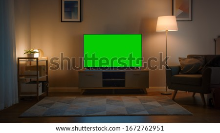 Shot of a TV with Horizontal Green Screen Mock Up. Cozy Evening Living Room with a Chair and Lamps Turned On at Home. #1672762951