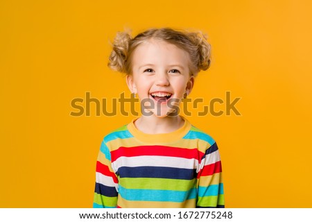 Cute little blonde girl smiling holding hands on the sides stands on a yellow background. a happy child in a multicolored striped jacket on a yellow background. space for text