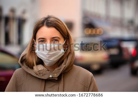 Woman wearing face mask during coronavirus outbreak. Virus spread flu prevention carantine. Girl in a facemask on a streets of Italy Royalty-Free Stock Photo #1672778686
