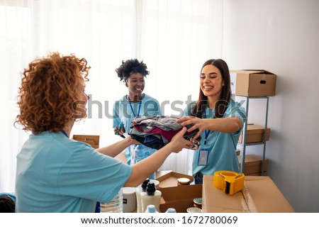Volunteers Collecting Food Donations In Warehouse. Team of volunteers holding donations boxes in a large warehouse. Volunteers putting clothes in donation boxes, social worker making notes charity #1672780069