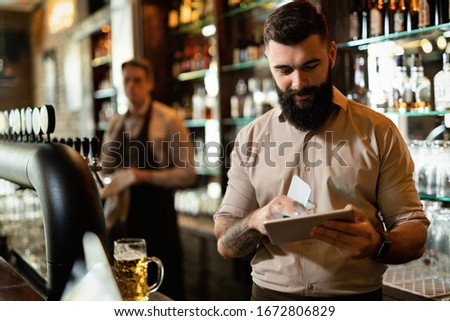 Young happy barista working in a bar and surfing the net on touchpad.  #1672806829