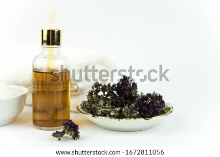 Spa treatment bottle of natural organic oil essence serum collagen. Towel, aromatic sea salt, herbs and flowers on white background. Copy space for text. Oil drop. #1672811056