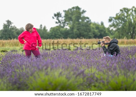 A young boy takes a picture of a woman in a lavender field in Poland.