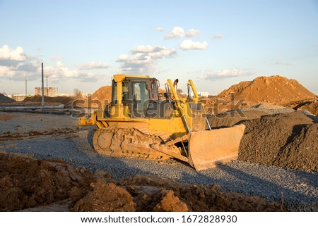 Dozer working at construction site. Bulldozer for land clearing, grading, pool excavation, utility trenching and foundation digging. Crawler tractor and earth-moving equipment #1672828930