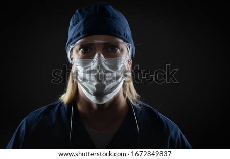 Female Medical Worker Wearing Protective Face Mask and Gear Against Dark Background. Royalty-Free Stock Photo #1672849837