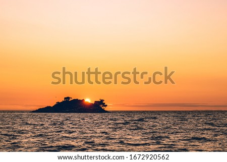 Romantic view of sunset over a deserted island in the distance at sea. View of the sea on the horizon. Royalty-Free Stock Photo #1672920562