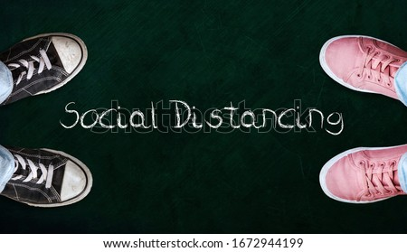 Two people standing on chalkboard with the word social distancing in between. Concept of staying physically apart for infection control intended to stop or slow down the spread of COVID-19 conoravirus #1672944199