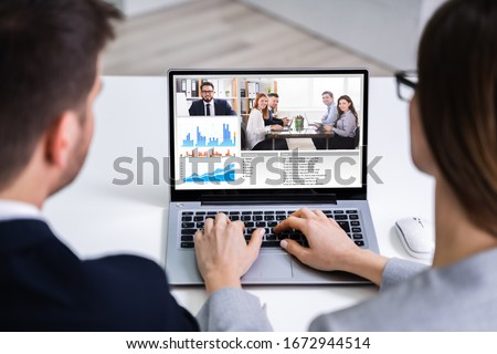 Two Young Businesspeople Video Conferencing On Computer At Office #1672944514