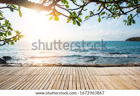 Terrace view sea tree sunlight wooden table on the beach landscape nature with sunset or sunrise / wooden bridge balcony view seascape idyllic seashore silhouette tropical tree summer vacation beach  Royalty-Free Stock Photo #1672963867
