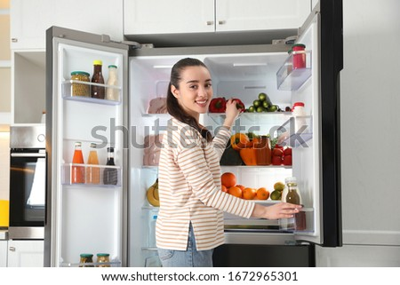 Young woman taking bell pepper out of refrigerator in kitchen #1672965301