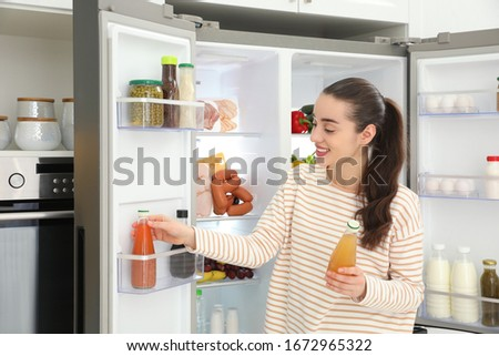 Young woman taking juice out of refrigerator in kitchen #1672965322