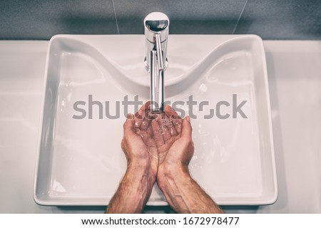 Washing hands with soap at work bathroom sink man hand care hygiene for coronavirus outbreak prevention. Corona Virus pandemic precaution by washing hands frequently for 20 seconds. Royalty-Free Stock Photo #1672978477