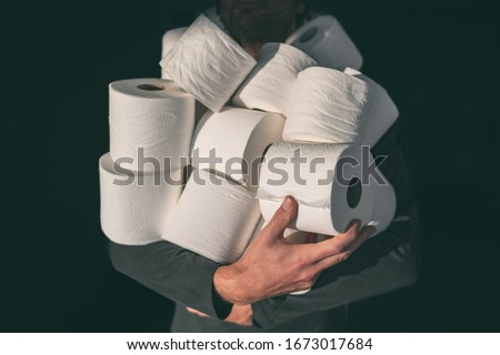 Toilet paper shortage coronavirus panic buying man hoarding carrying many rolls at home in fear of corona virus outbreak closing shopping stores. Royalty-Free Stock Photo #1673017684