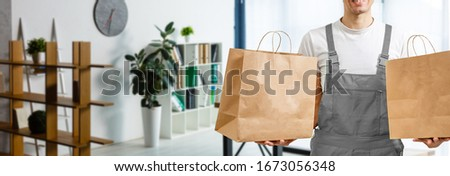 Young man holding paper bag, close-up. Wearing t-shirt, light grey background. Food delivery. #1673056348