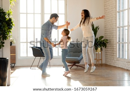 Full length overjoyed family of three having fun together. Smiling young father holding hands of happy little daughter, dancing together to favorite music while joyful mother jumping singing song. #1673059267
