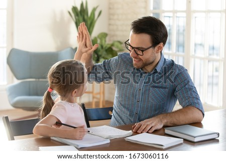 Happy young dad giving high five to smiling little daughter, satisfied with homework. Joyful male tutor praising small girl with successful exercise finish. Home schooling children education concept. Royalty-Free Stock Photo #1673060116