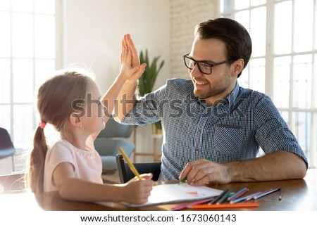 Head shot happy little child girl giving high five to affectionate loving father, finishing drawing picture together at home. Smiling young dad celebrating good work done with cute small daughter.