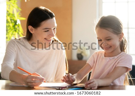 Head shot young happy babysitter tutor educating little preschool child girl, sitting together at table. Smiling mother helping small daughter drawing coloring picture, early development concept.