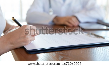 Close up young woman holding pen, ready to sign medical insurance contract with family doctor. Female patient putting signature on agreement with physician during meeting in clinic hospital.