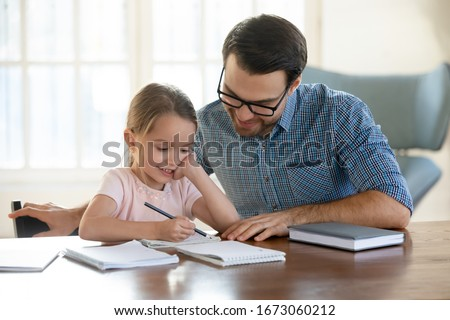 Young father in eyeglasses pleased to see little daughters' study success. Excited smiling small child girl enjoying learning with pleasant dad at home. Children education, home schooling concept. Royalty-Free Stock Photo #1673060212