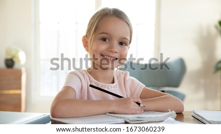 Head shot close up portrait of happy small pupil learning at home. Smiling little child girl enjoying doing lessons in living room. Smart kid schoolgirl looking at camera, studying remotely online. #1673060239