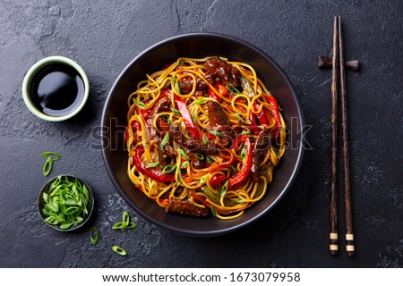 Stir fry noodles with vegetables and beef in black bowl. Slate background. Close up. Top view. #1673079958