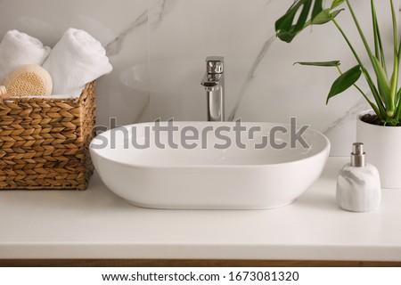 Stylish vessel sink on light countertop in modern bathroom #1673081320