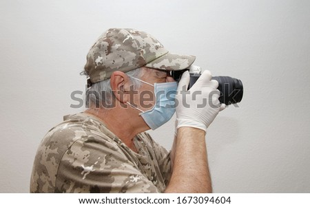 photographer in camouflage clothing, mask and latex gloves as a precaution not to get infected by covid-19, coronavirus, taking pictures with his camera