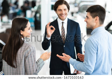 Nice Choice. Happy young couple talking about new car purchase, auto sales manager showing okay sign in the background #1673103163