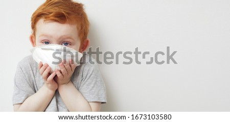 Little boy beeing frighten for the corona virus covid-19 / 2019-nCov while looking in to the camera #1673103580