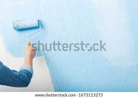 Paints texture wall with roller in blue, free space #1673113273