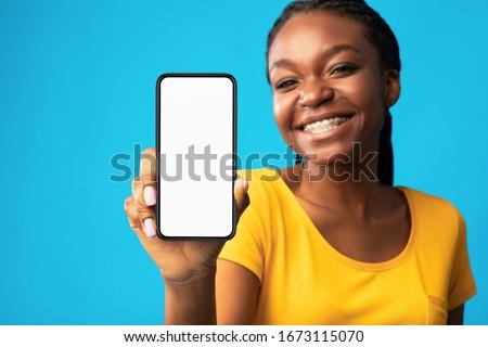 Black Girl Showing Smartphone Blank Screen Smiling At Camera Recommending Mobile App Over Blue Studio Background. Selective Focus, Mockup #1673115070