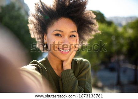 Portrait beautiful young african american woman taking selfie outdoors #1673133781