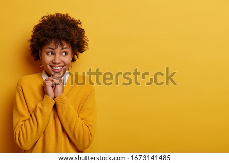 Portrait of happy ethnic girl anticipates something awesome happen, looks happily aside, keeps hands together near face, has glad expression, appealing smile, isolated on yellow studio background #1673141485