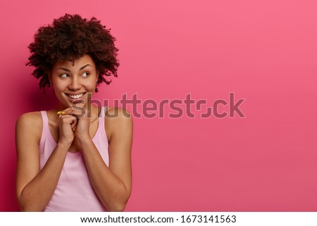 Horizontal shot of attractive dark skinned girl looks aside with smile, keeps hands under chin, sees something appealing right, poses against pink background, blank space for your promotion. #1673141563