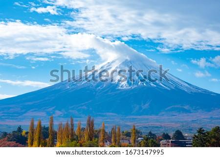 Japan. Mount Fuji. Snow on top of volcano Fujiyama. Clouds cover the top of Mount Fujiyama. Landscapes of Japan. Mount Fuji in the background of blue sky with clouds. Natural attractions of Japan #1673147995