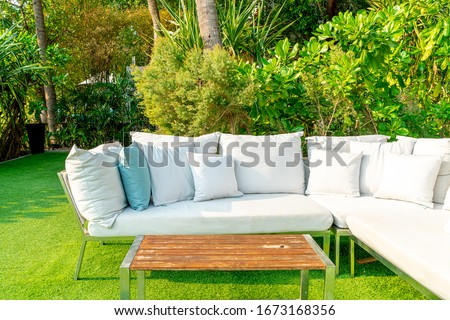 comfortable pillows on outdoor patio chair and table in garden #1673168356