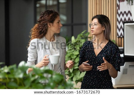 Diverse employees chatting during coffee break, walking in modern office, Asian businesswoman wearing glasses sharing ideas, discussing project with colleague, having pleasant conversation Royalty-Free Stock Photo #1673172670