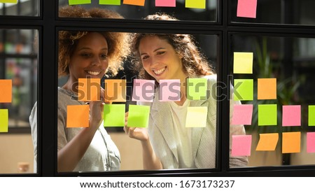 Smiling diverse colleagues discussing creative startup ideas on sticky papers on scrum glass board close up, successful employees looking at stickers, brainstorming, planning new project, writing Royalty-Free Stock Photo #1673173237