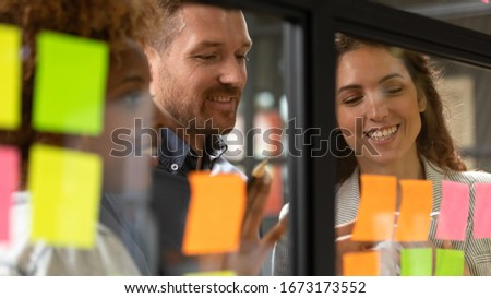 Creative diverse employees team writing ideas on sticky papers on glass wall close up, multiethnic colleagues brainstorming, working on new project plan together at briefing, looking at stickers Royalty-Free Stock Photo #1673173552