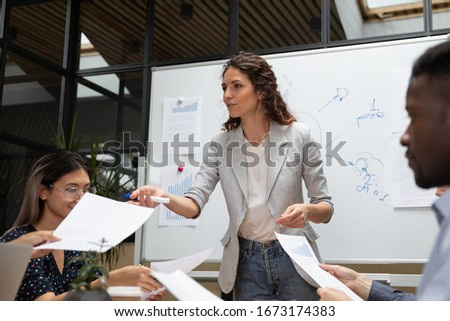 Confident businesswoman mentor speaking, presenting results to investors at corporate meeting close up, negotiations, business coach explaining marketing plan to diverse employees reading documents Royalty-Free Stock Photo #1673174383