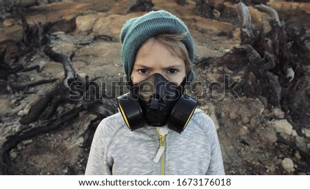 Environmental pollution, ecological disaster, nuclear war, post apocalypse concept. Care for future generations. Child in protective mask, face-guard to prevent breathing toxic air. Covid-19, Coronav Royalty-Free Stock Photo #1673176018