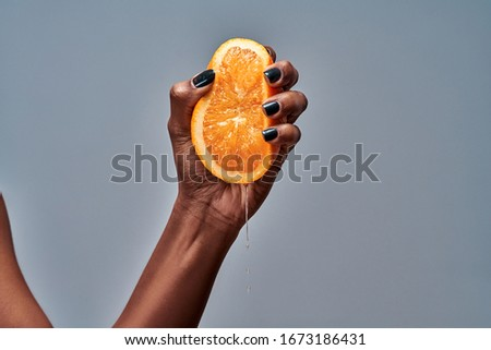 Female hand squeezing orange isolated on grey. Copy space #1673186431